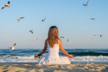 picture of woman on the beach meditating to manifest abundance and joy